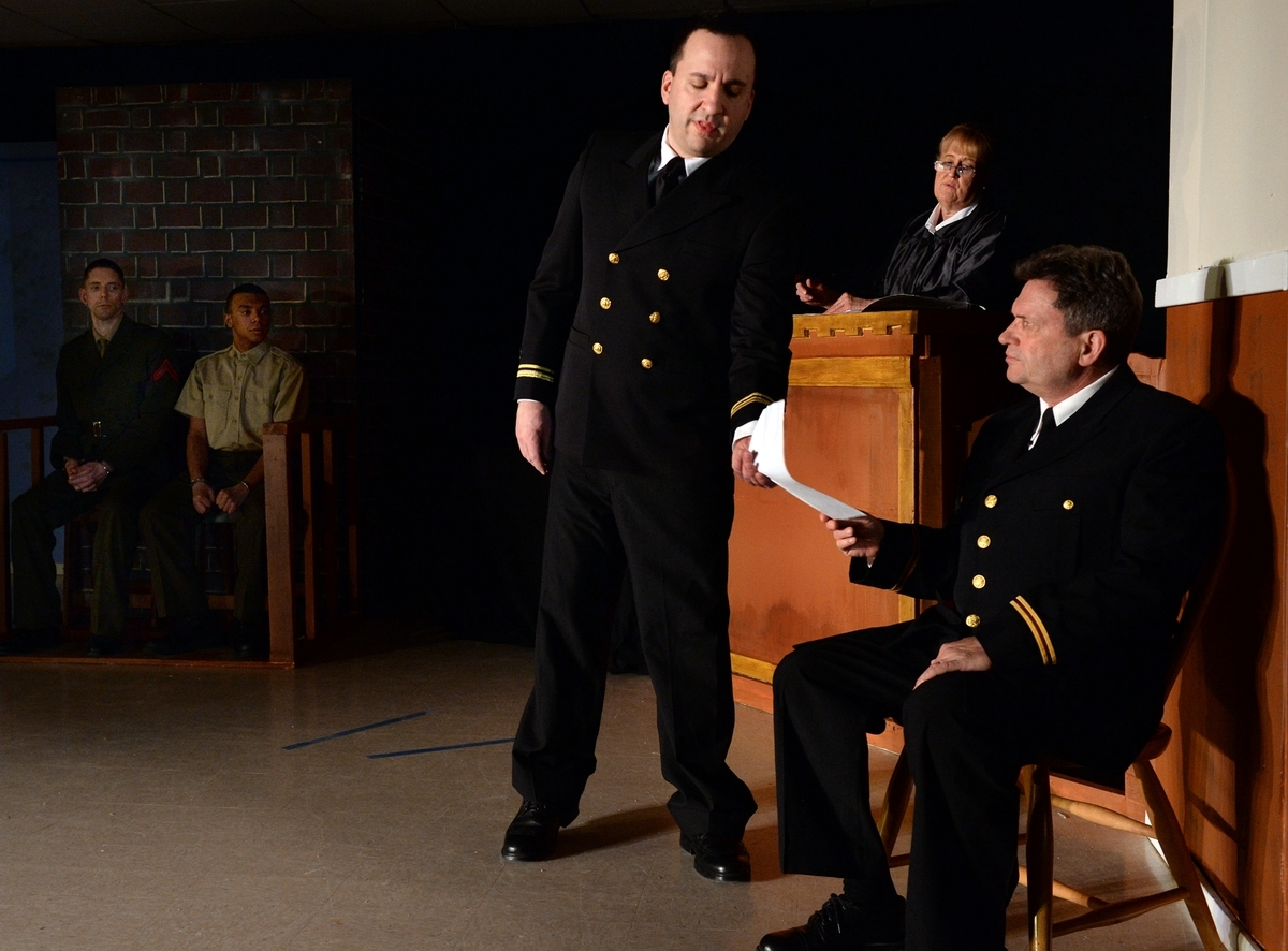 <b></b> Ken Schroeder, center, portraying Lt. j.g. Daniel A. Kaffee questions Andy Plasse, right, portaying the doctor Cmdr. Walter Stone, in a scene during rehearsal of the Groton Regional Theatre production of