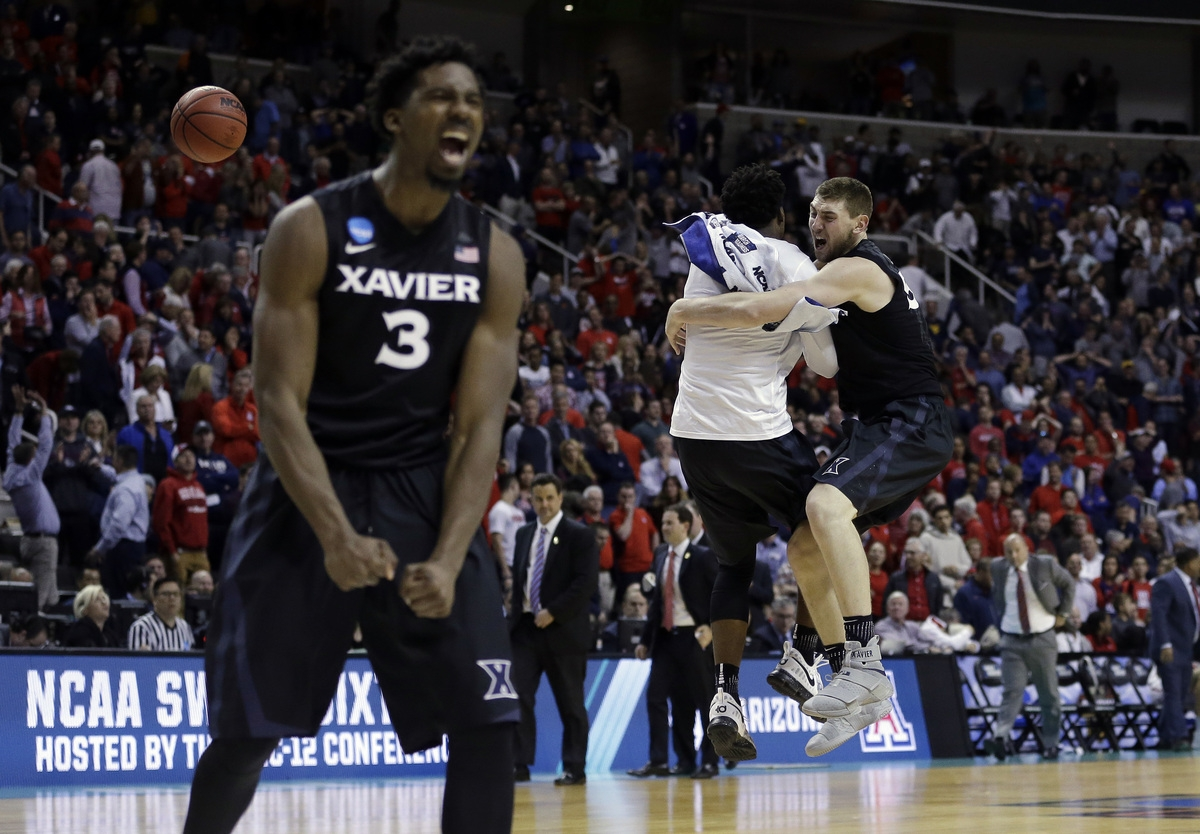 <b></b> Xavier players including Quentin Goodin (3) and Sean O'Mara, right, celebrate after stunning Arizona on Thursday night, 73-71, to win its NCAA Tournament regional semifinal in San Jose, Calif. (Ben Margot/AP Photo)