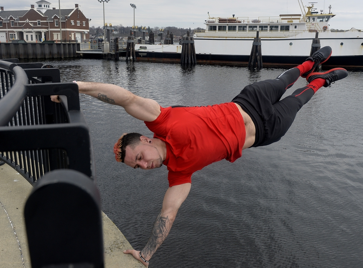 <b></b> Samer Delgado, a personal trainer and calisthenics enthusiast, holds a human flag pose while training on Wednesday, April 12 at Waterfront Park in New London. The New London resident will compete in