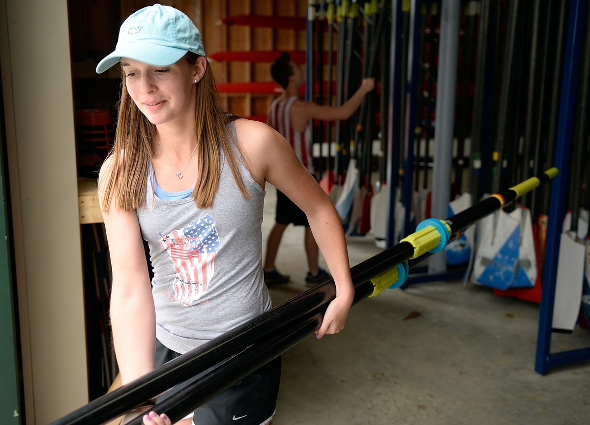 <b></b> Old Lyme senior rower Caleigh O'Neil carries oars to the dock before heading out on the waters of Rogers Lake for crew practice on Thursday. The two-sport star, who scored the game-winning goal when the Wildcats beat Old Saybrook 1-0 in the 2016 Class S state soccer final, has accepted a Division I scholarship to row at UMass. (Sean D. Elliot/The Day)
