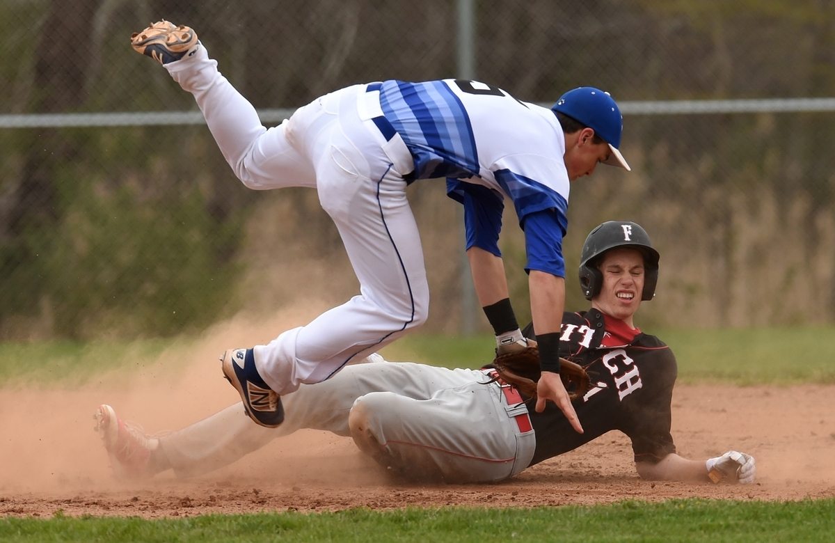 <b></b> Old Lyme second baseman Jace Funaro is upended by Fitch's Hendrick Khoury after getting a force at second and throwing to first during Monday's baseball game at Old Lyme. Fitch defeated the Wildcats 5-3. (Dana Jensen/The Day)