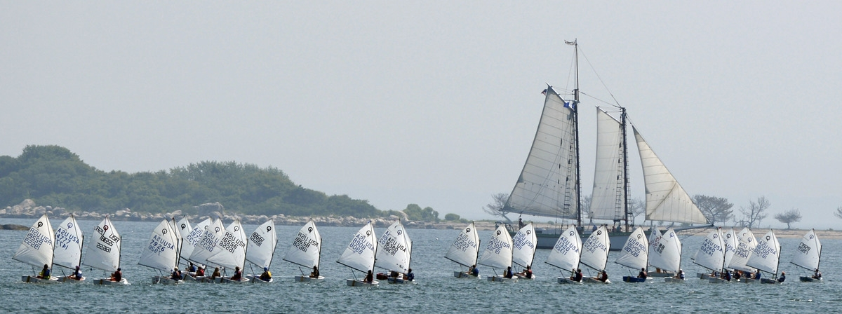 <b></b> In this July 2015 Day file photo, Optimist class sailboats race in Fishers Island Sound off Morgan Point in Noank as the schooner Argia passes on a day-sail.  Visitors and residents to downtown Mystic this summer will see that the schooner Argia has returned to its original berth at Steamboat Wharf, just south of the drawbridge.  (Sean D. Elliot/The Day)