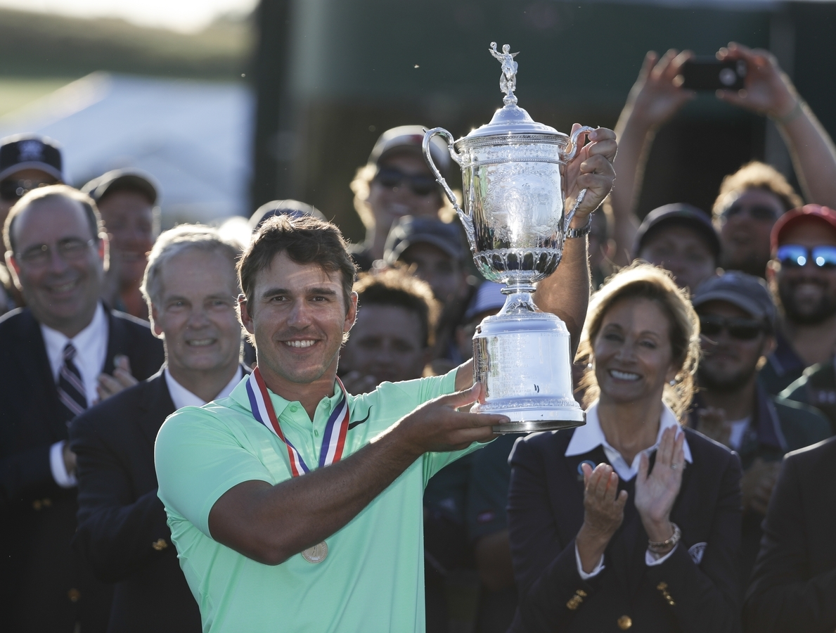 <b></b> Brooks Koepka holds up the trophy after winning the U.S. Open on Sunday at Erin Hills in Erin, Wis. (AP Photo/Chris Carlson)