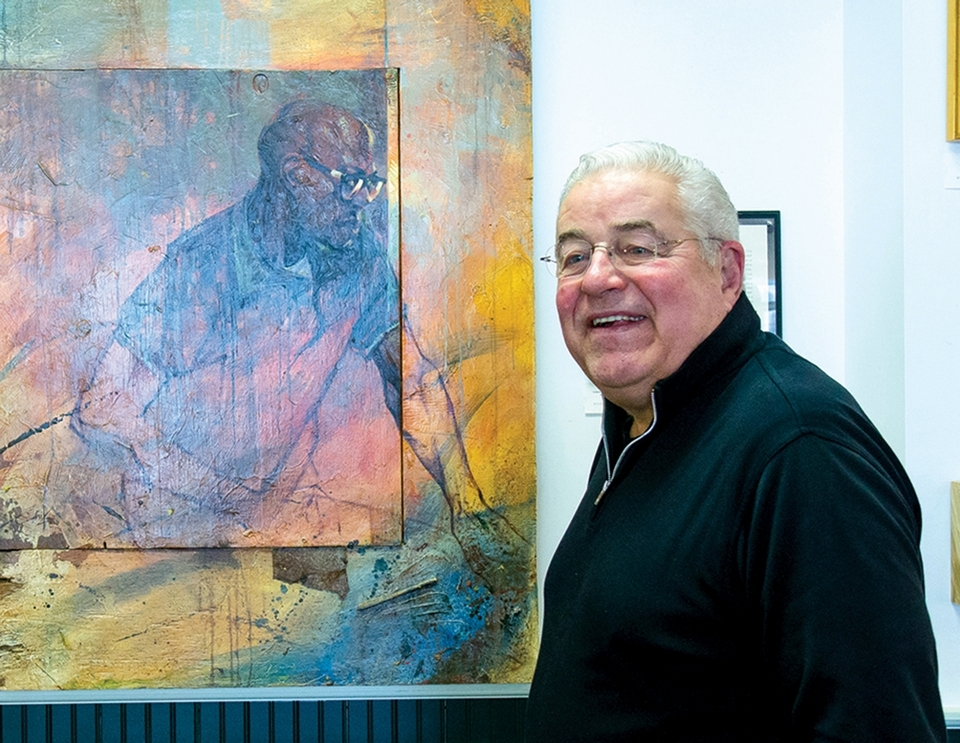 Proprietor John Johnson stands before one of the signature pieces in the gallery's collectio,