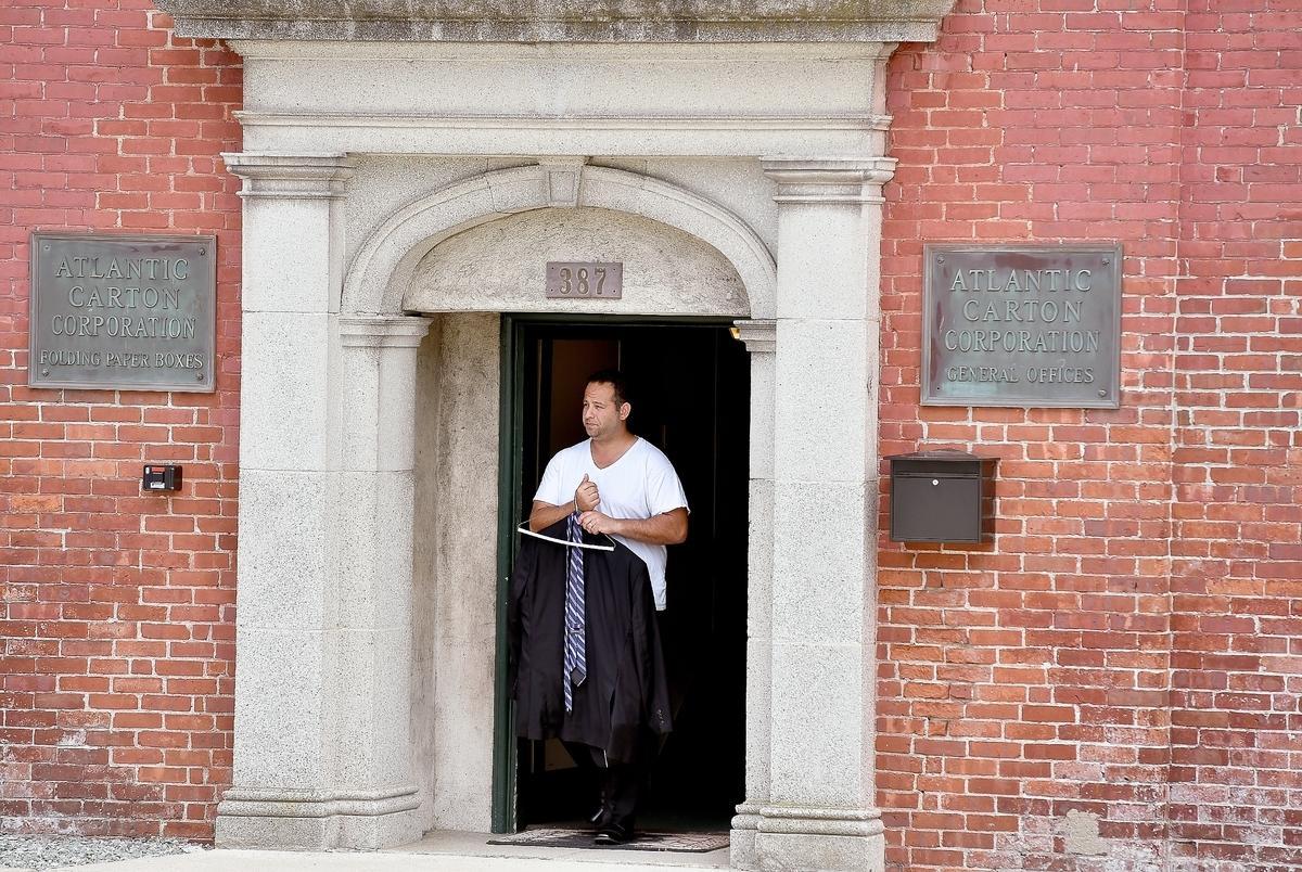 <b></b> A representative of Maltz Auctions, based in Long Island, N.Y., exits the front entrance of the former Atlantic Packaging Corp. building on North Main Street in Norwich, which was auctioned off on Wednesday, June 21, 2017. (Tim Martin/The Day)