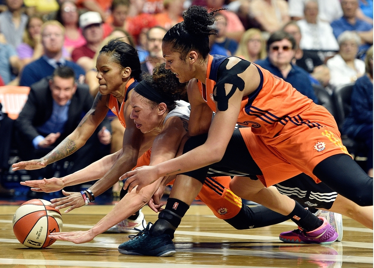 <b></b> Connecticut forward Alyssa Thomas, front, and guard Courtney Williams, back, battle San Antonio's Dearica Hamby for a loose ball during the second half of the Sun's 89-75 victory over the Stars in a WNBA game on Sunday at Mohegan Sun Arena. (Sean D. Elliot/The Day)