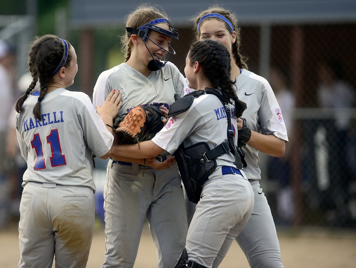 <b></b> Waterford pitcher Maddie Burrows, is hugged by catcher Abby Maynard while Emma Marelli (11) and Milena Walker, right, join the celebration after Waterford defeated Wesport 10-3 on Tuesday night to win the Connecticut Little League 11-12-year-old softball championship at Elm Ridge Park in Cromwell. (Sarah Gordon/The Day)