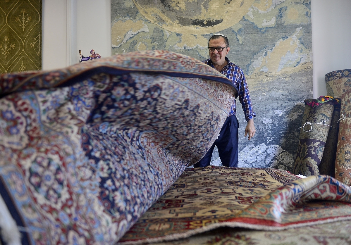 <b></b> Masood Banilivy, of Banilivy Rug Corporation, throws back rugs into place on Wednesday, Aug. 16, 2017, at the shop on Roosevelt Avenue in Mystic.  The new shop offers a unique selection of hand woven rugs from around the world as well as professional cleaning and restoration services. (Sarah Gordon/The Day)