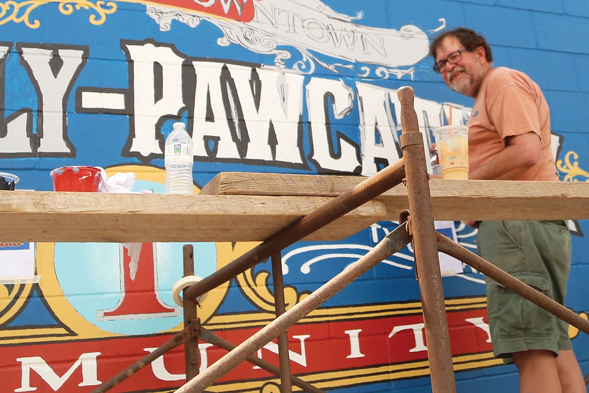 <b></b> Cam Bortz is the designer and Walldog project leader of the Westerly-Pawcatuck welcome sign murals on 87 Main St., Westerly, takes a moment to smile Friday night. Bortz has been a Walldog muralist for 20 years and owns Finest Kind Signs in Pawcatuck.