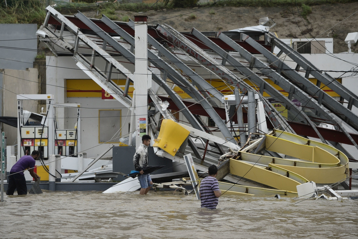 <b></b> People walk next to a gas station flooded and damaged by the impact of Hurricane Maria, which hit the eastern region of the island, in Humacao, Puerto Rico, Wednesday, September 20, 2017. The strongest hurricane to hit Puerto Rico in more than 80 years destroyed hundreds of homes, knocked out power across the entire island and turned some streets into raging rivers in an onslaught that could plunge the U.S. territory deeper into financial crisis. (AP Photo/Carlos Giusti)