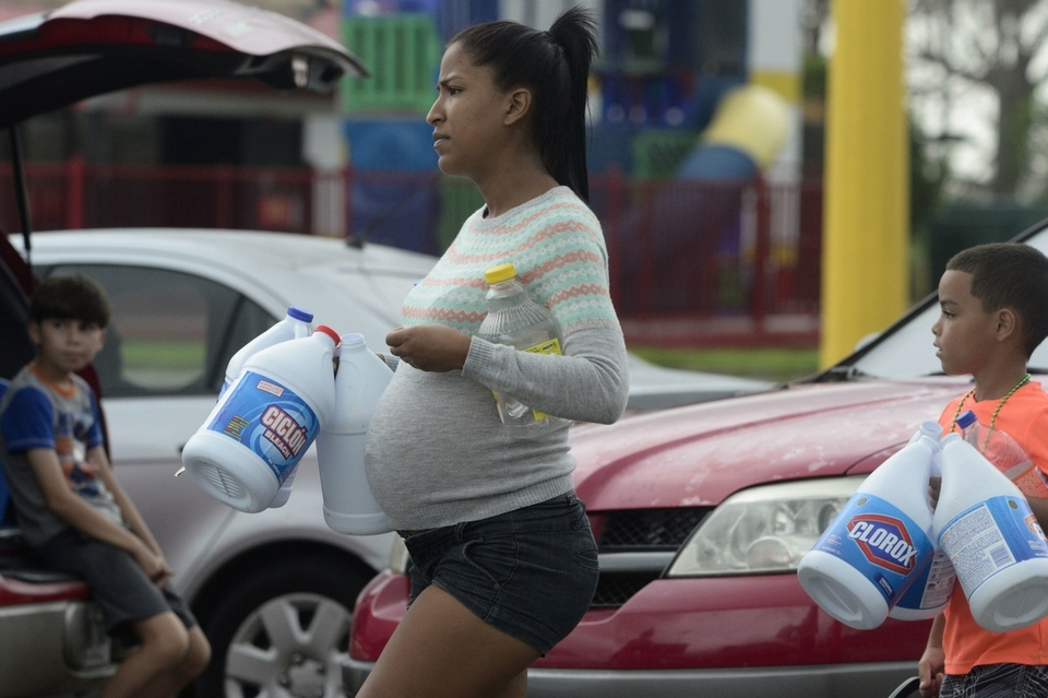 A pregnant woman carries empty plastic bottles to collect water a day after the impact of Hurricane Maria, in Yabucoa, Puerto Rico, Thursday, September 21, 2017. (AP Photo/Carlos Giusti)
