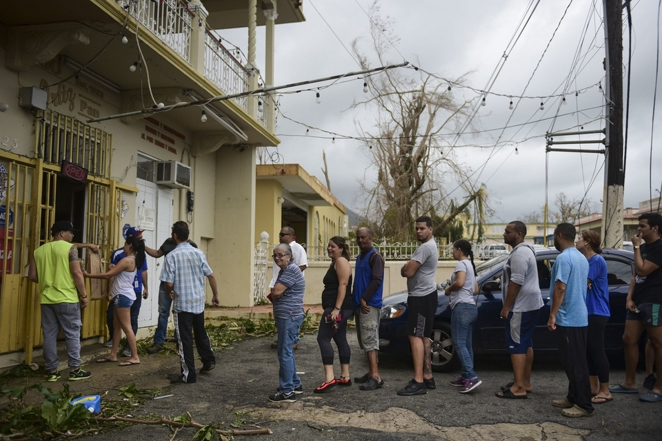 People wait in line to buy bread at Ortiz bakery after the passing of Hurricane Maria, in Yabucoa, Puerto Rico, Thursday, September 21, 2017.  (AP Photo/Carlos Giusti)