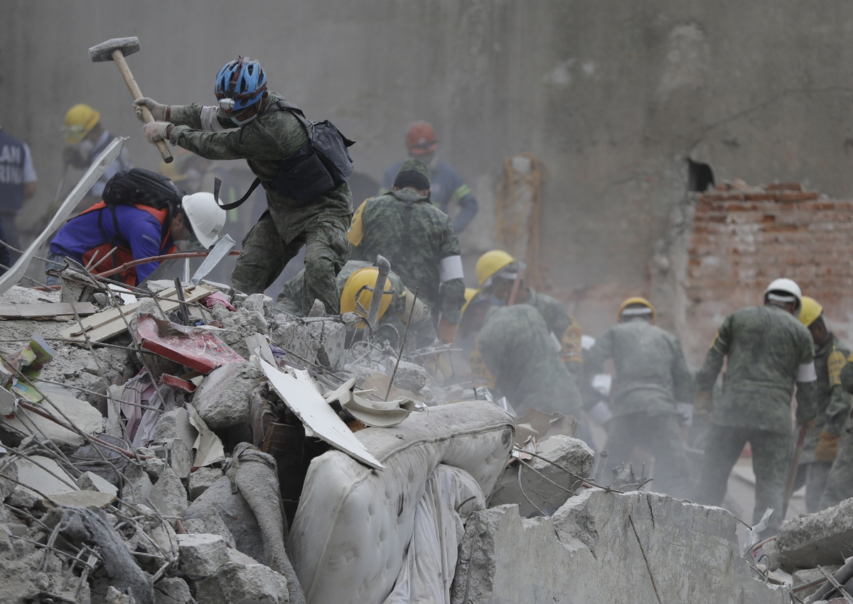 <b></b> Rescue workers search for survivors at an apartment building located on Amsterdam street, at the intersection with Laredo street, that collapsed during an earthquake in the Condesa neighborhood of Mexico City, Mexico, Thursday, Sept. 21, 2017. Tuesday's magnitude 7.1 earthquake has stunned central Mexico, killing more than 200 people as buildings collapsed in plumes of dust. (AP Photo/Natacha Pisarenko)
