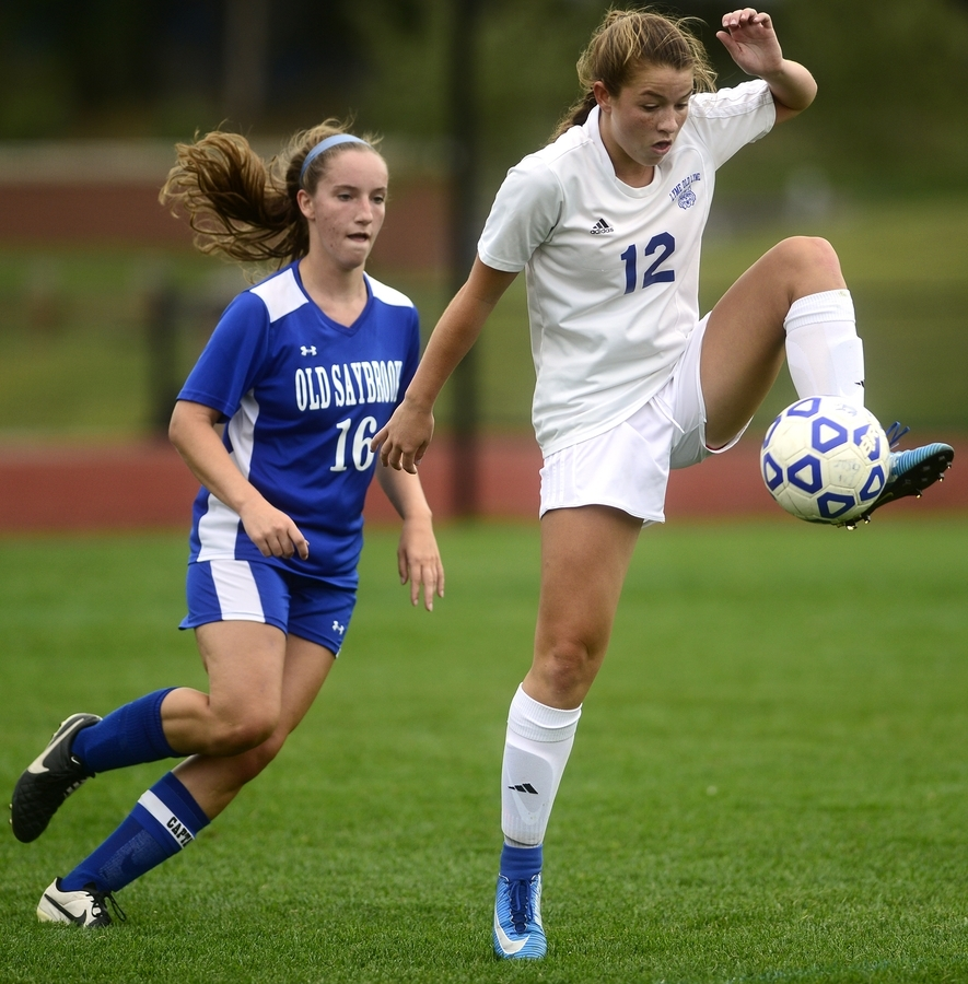 <b></b> Old Lyme's Mya Johnson (12) traps the ball in front of Old Saybrook's Kendall Hartt during Thursday's girls' soccer game at Old Lyme. Johnson scored a pair of goals as the Wildcats beat the Rams 3-0 in a rematch of the 2016 Class S state final, which Old Lyme won 1-0. (Sarah Gordon/The Day)
