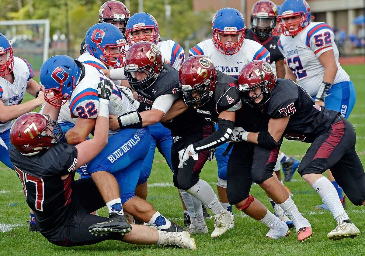 <b></b> Valley Regional/Old Lyme's Ian Neviaser (77) drags down Coginchaug/Hale-Ray's Patrick Ladas (22) with the help from teammates Michael Cullina (13), Blair Allen (4) and Joshua Donahue (35) during the Warriors' 41-13 win on Saturday at Old Lyme High School. (Sean D. Elliot/The Day)