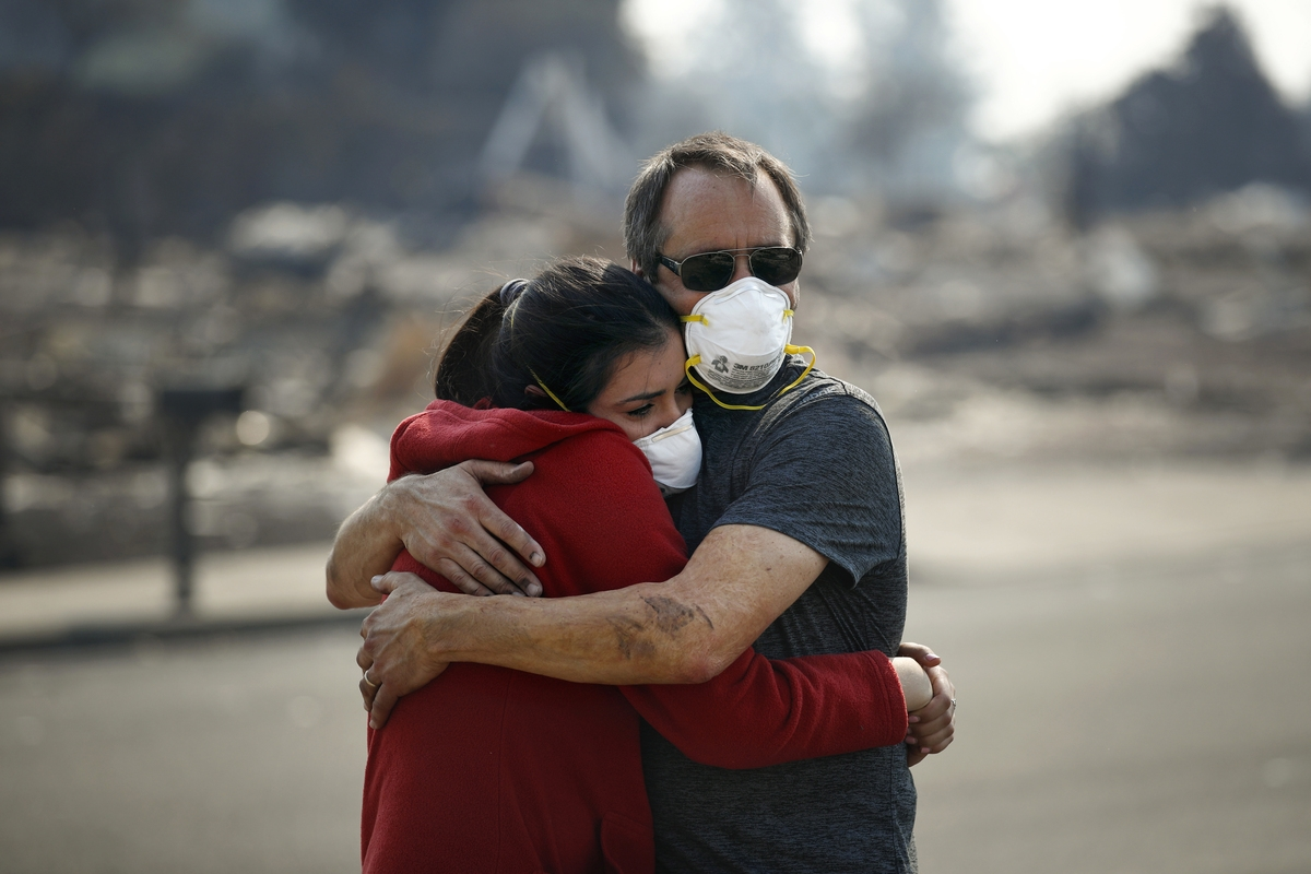 <b></b> Howard Lasker, right, comforts his daughter, Gabrielle, who is visiting their home for the first time since a wildfire swept through it Sunday, Oct. 15, 2017, in Santa Rosa, Calif. With the winds dying down, fire officials said Sunday they have apparently
