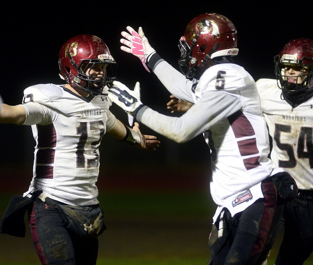 <b></b> Valley/Old Lyme's Michael Cullina (13) celebrates a touchdown with teammate Ernest Jean-Pierre during Friday night's 22-7 win over rival Haddam-Killingworth. The Warriors clinched a Class S state playoff berth and the Peqout Sassacus Divisoin title with the win. (Sarah Gordon/The Day)