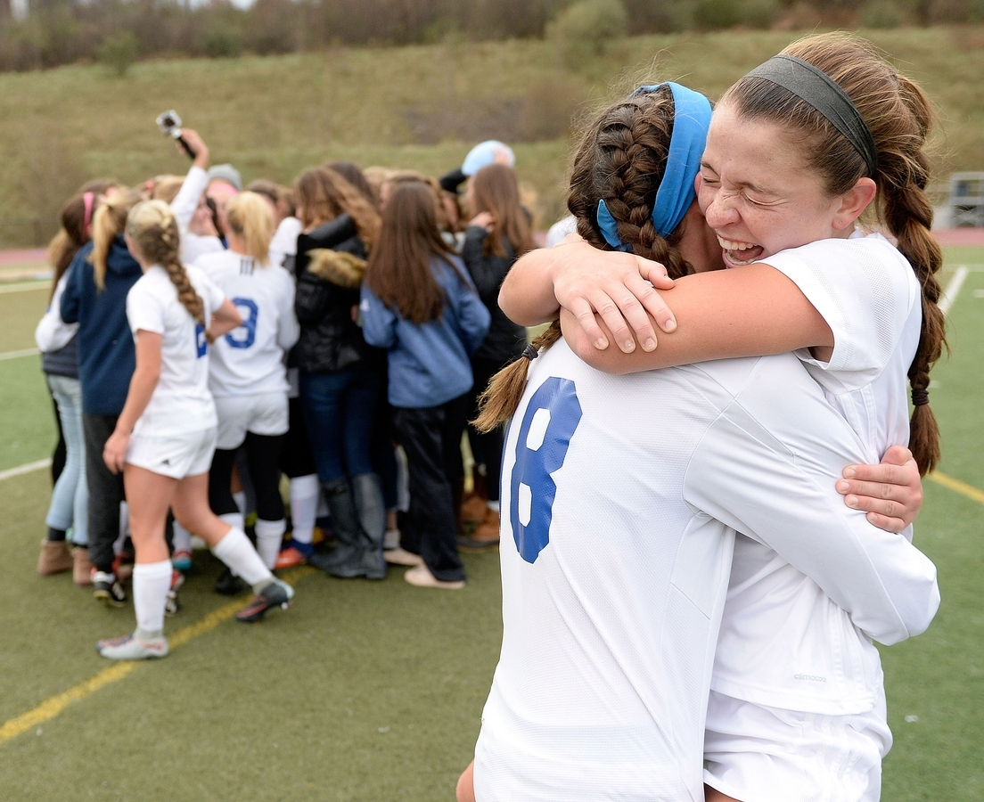 <b></b> Old Lyme's Mya Johnson, right, and Caroline Wallace embrace as the Wildcats celebrate their 2-1 double overrtime win over Holy Cross in Saturday's CIAC Class S state championship girls' soccer game at Middletown High School. Johnson scored off a header in overtime to give the Wildcats their third consecutive state title. (Sean D. Elliot/The Day)
