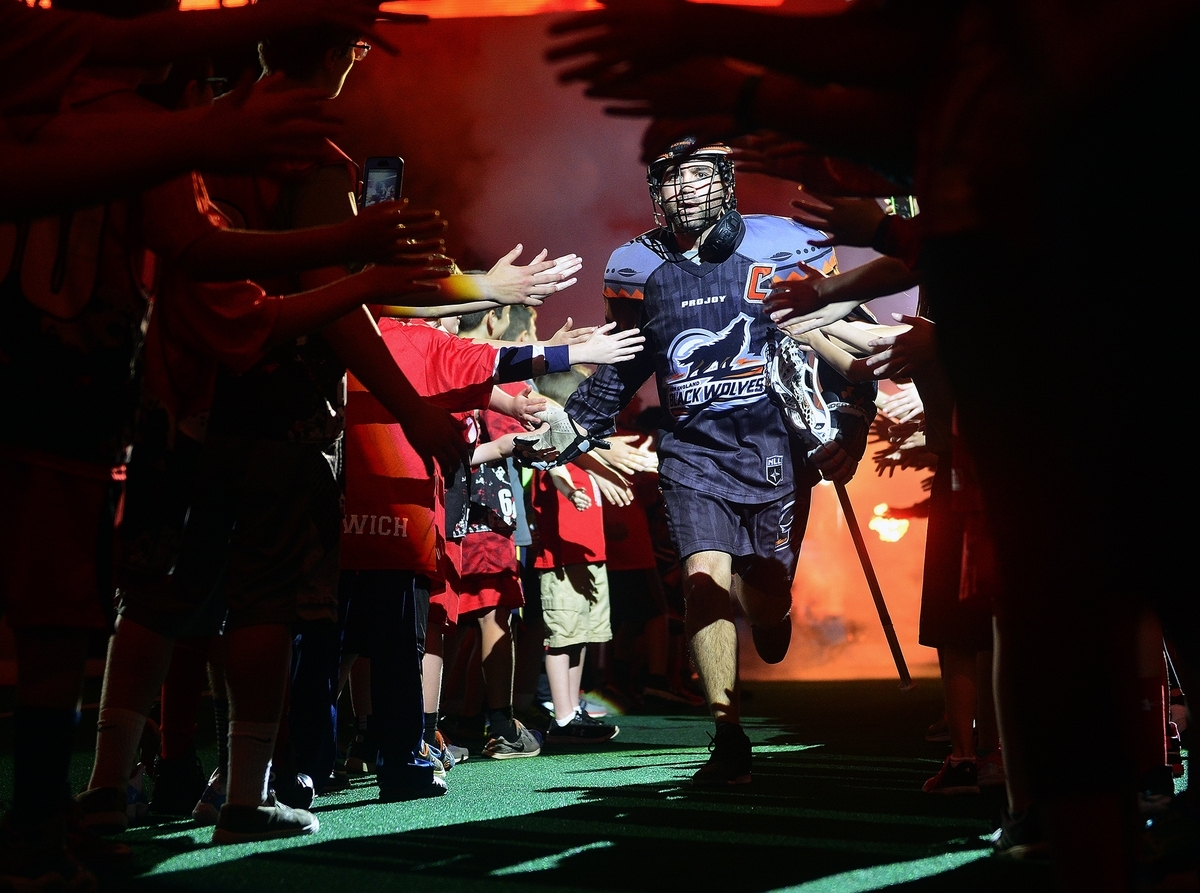<b></b> New England Black Wolves captain Shawn Evans high-fives fans as he runs onto the field before a game last season at Mohegan Sun Arena. The Black Wolves, with a revamped defense, open the 2017-18 season Friday at home against the Georgia Swarm. (Sarah Gordon/Day File Photo)