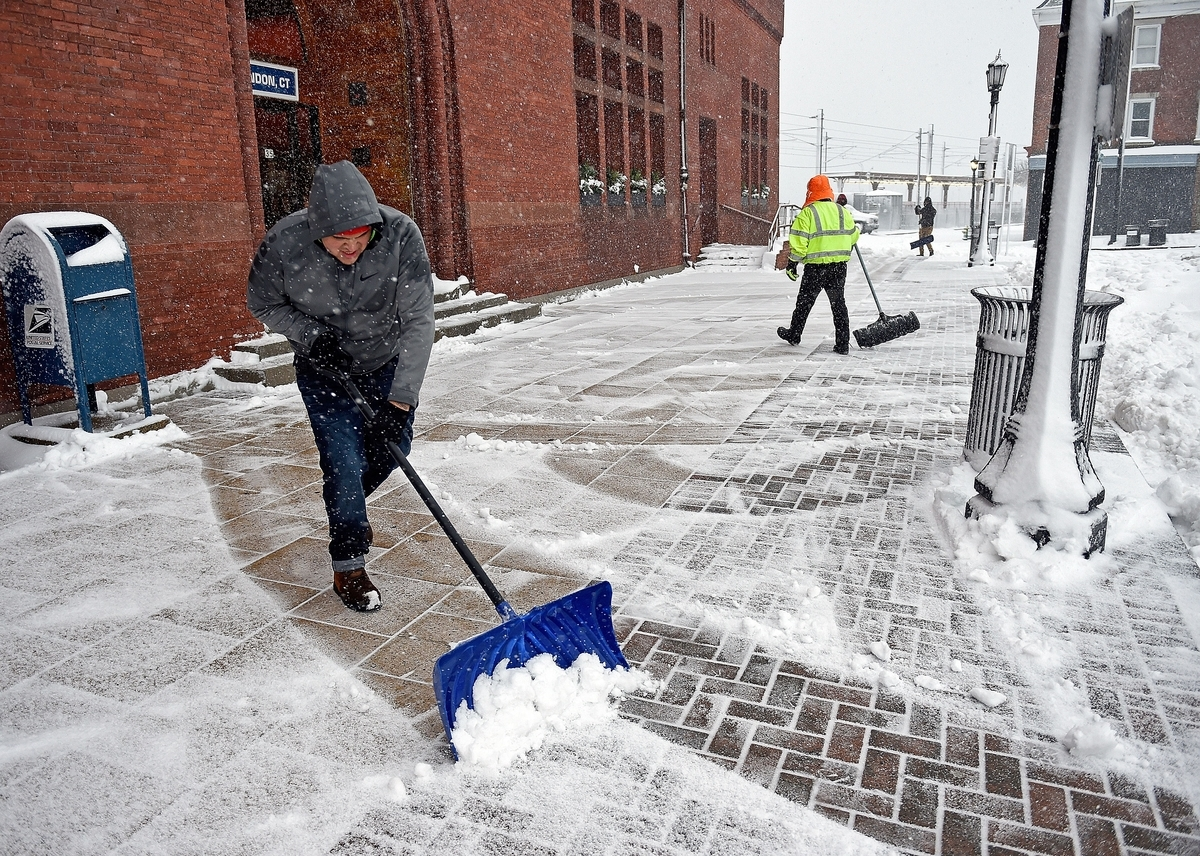 <b></b> Jacob Mena with Luis Manuel Co. shovels snow in front of Union Station on Feb. 9, 2017, in New London. (Sean D. Elliot/The Day)