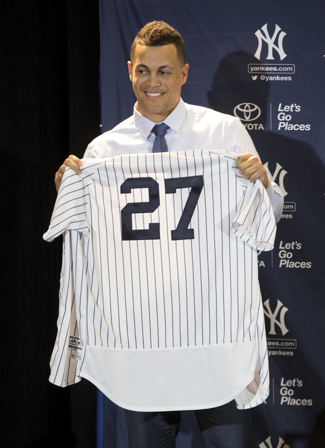<b></b> Giancarlo Stanton of the New York Yankees shows off his new jersey during the Major League Baseball winter meetings in Orlando, Fla., on Monday. (Willie J. Allen Jr./AP Photo)