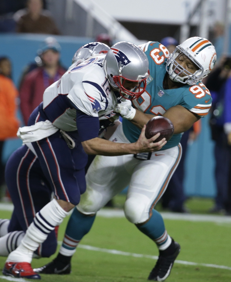 <b></b> Patriots quarterback Tom Brady (12) is sacked by Miami's Ndamukong Suh (93) during the second half of Monday night's game in Florida. The Dolphins' ended New England's eight-game winning streak with a 27-20 win. (AP Photo/Lynne Sladky)