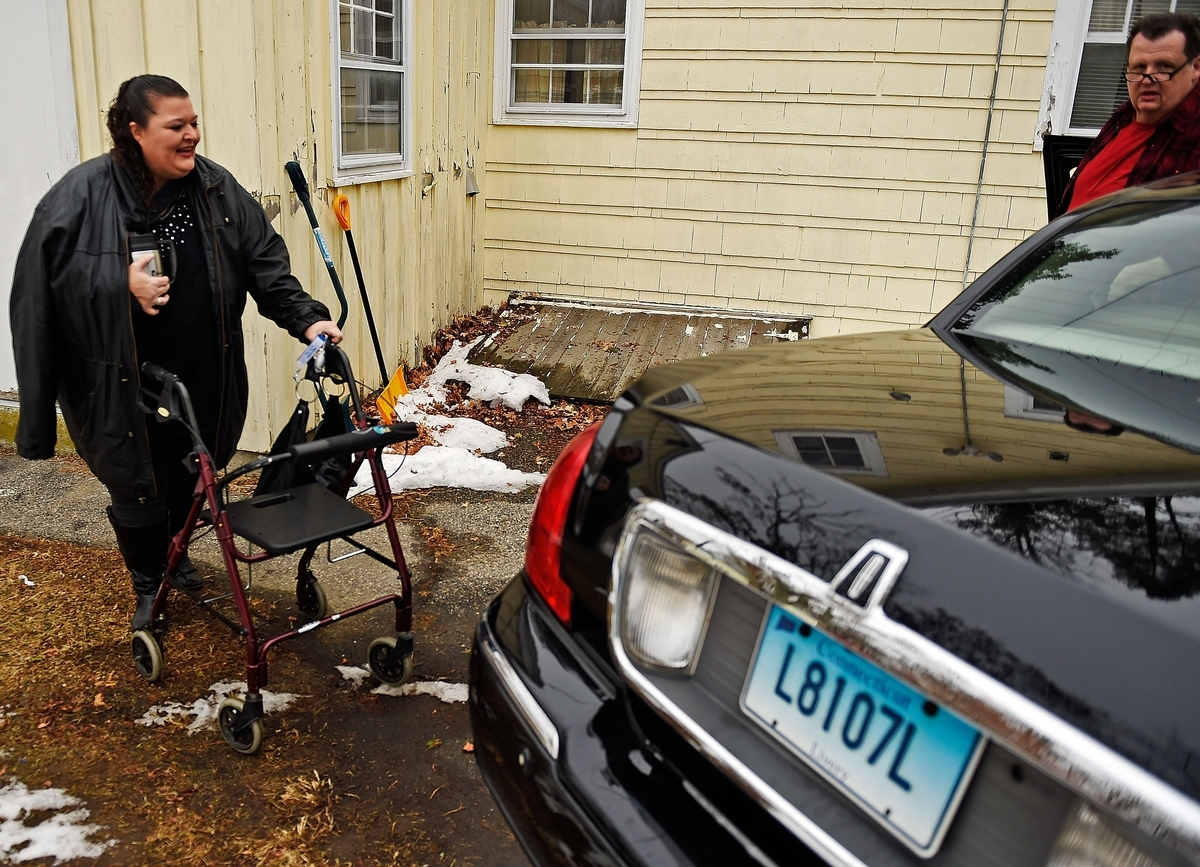 <b></b> Tricia Volpe greets her livery driver, Arthur Daniel from Harry's Taxi, Thursday, Jan. 11, 2018, at her Groton home. (Sean D. Elliot/The Day)