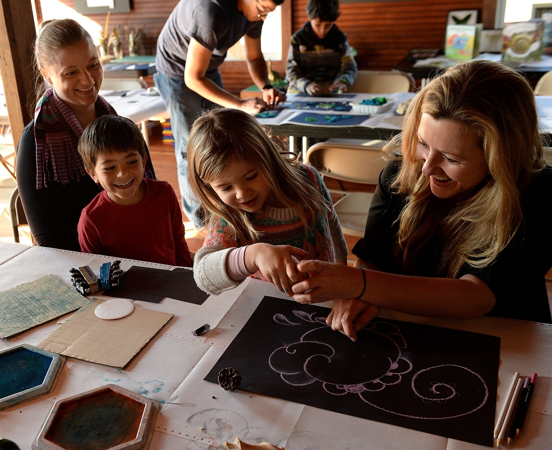 <b></b> Alayna Atlixqueno, left, of Ledyard and her son, Gabriel, 4, laugh while they watch Liz Lomax, right, of Mystic and her daughter, Olivia, 4, check to see if there is anything living inside a shell while they attend the  Super Sunday: Creation Station family art event in the Art Barn at Coogan Farm Nature & Heritage Center in Mystic Sunday, Jan. 14, 2018.  The art projects on Sunday were to create artwork using patterns found in nature with the various art supplies available at different stations.  (Dana Jensen/The Day)