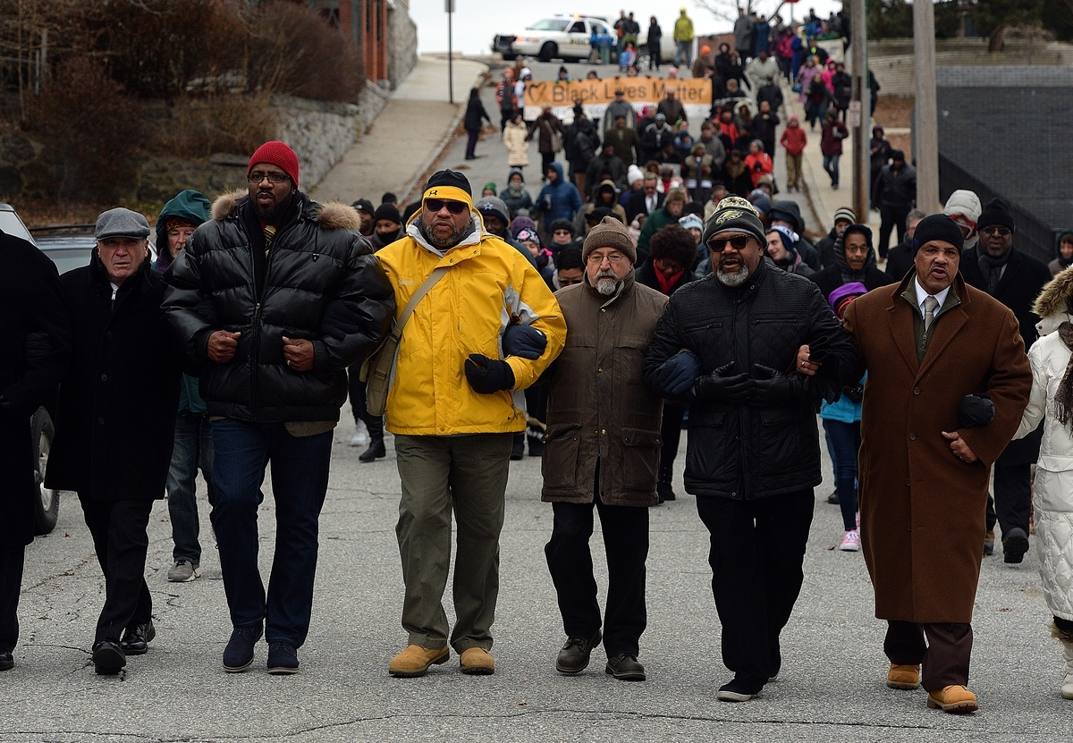 <b></b> From left, Mayor Michael Passero, Anthony Nolan, president of the city council, Jerry Mahan,  Michael Tranchida, city councilor, Wilbur Glenn and Rev. Marcus Luter, of Beulah Land Church of God in Christ, walk down Cottage Street during the annual Martin Luther King March from New London City Hall to Shiloh Baptist Church for a service, Monday, Jan. 15, 2018.  (Dana Jensen/The Day)