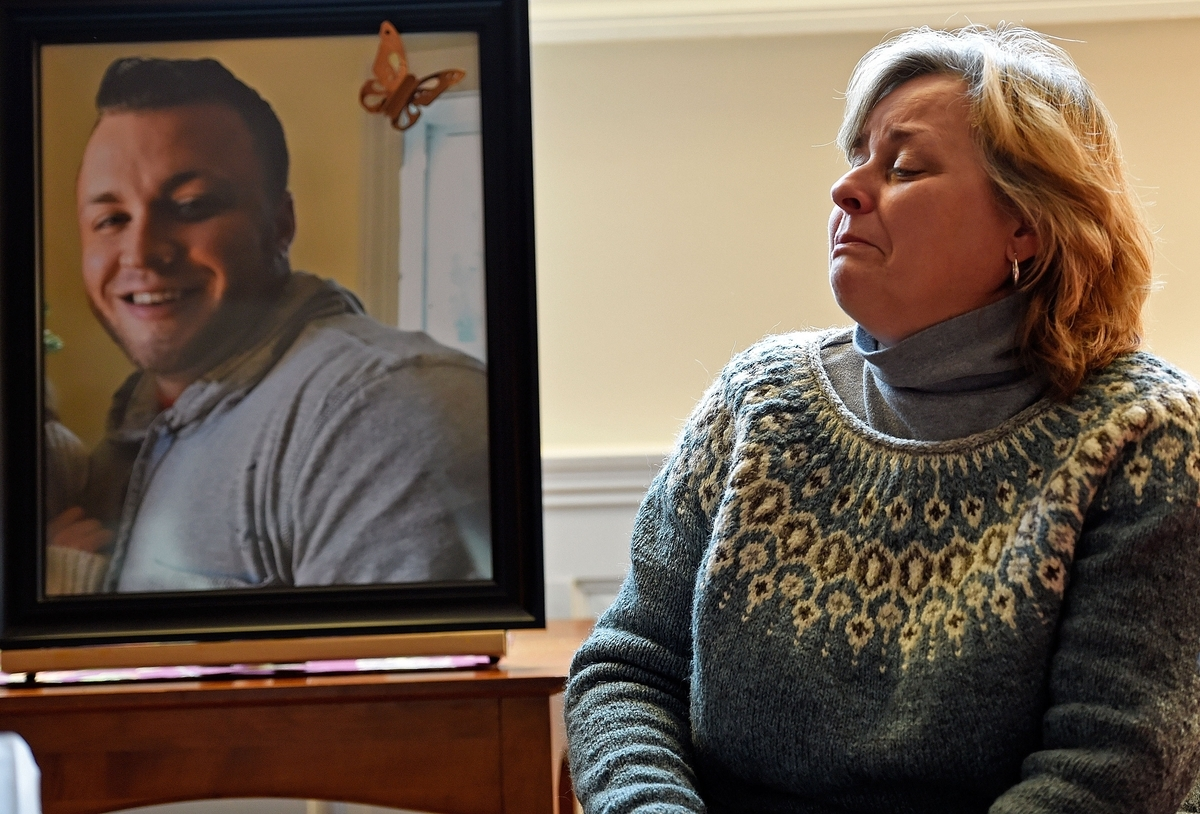 <b></b> Chris Majchrzak breaks down in tears as she and her husband, Mark, talk about their son Daniel, pictured at left, and his death from an opioid overdose, in their East Lyme home Monday, Jan. 15, 2018. Daniel, a 2010 graduate of East Lyme High School struggled with opioid addiction for six years and his family wanted to share the story of his battle after they were open about the cause of his death in his February 2017 obituary. (Sean D. Elliot/The Day)