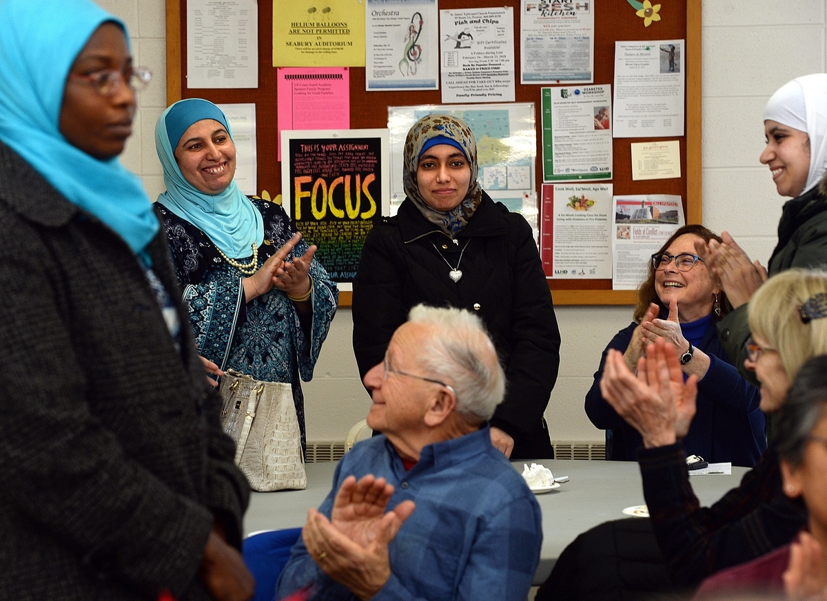 <b></b> Refugees Amna Azrag from Sudan, left, Halima Kabny, second from left, from Syria and her daughters, Khawla Kabny, center, and Toka Kabny, 15, right, all now of New London stand to be recognized during a celebration of welcoming refugees held at St. James Episcopal Church in New London Sunday, Jan. 21, 2018.  The Kabny family were the first Syrian refugees to come to New London in June 2016.  (Dana Jensen/The Day)