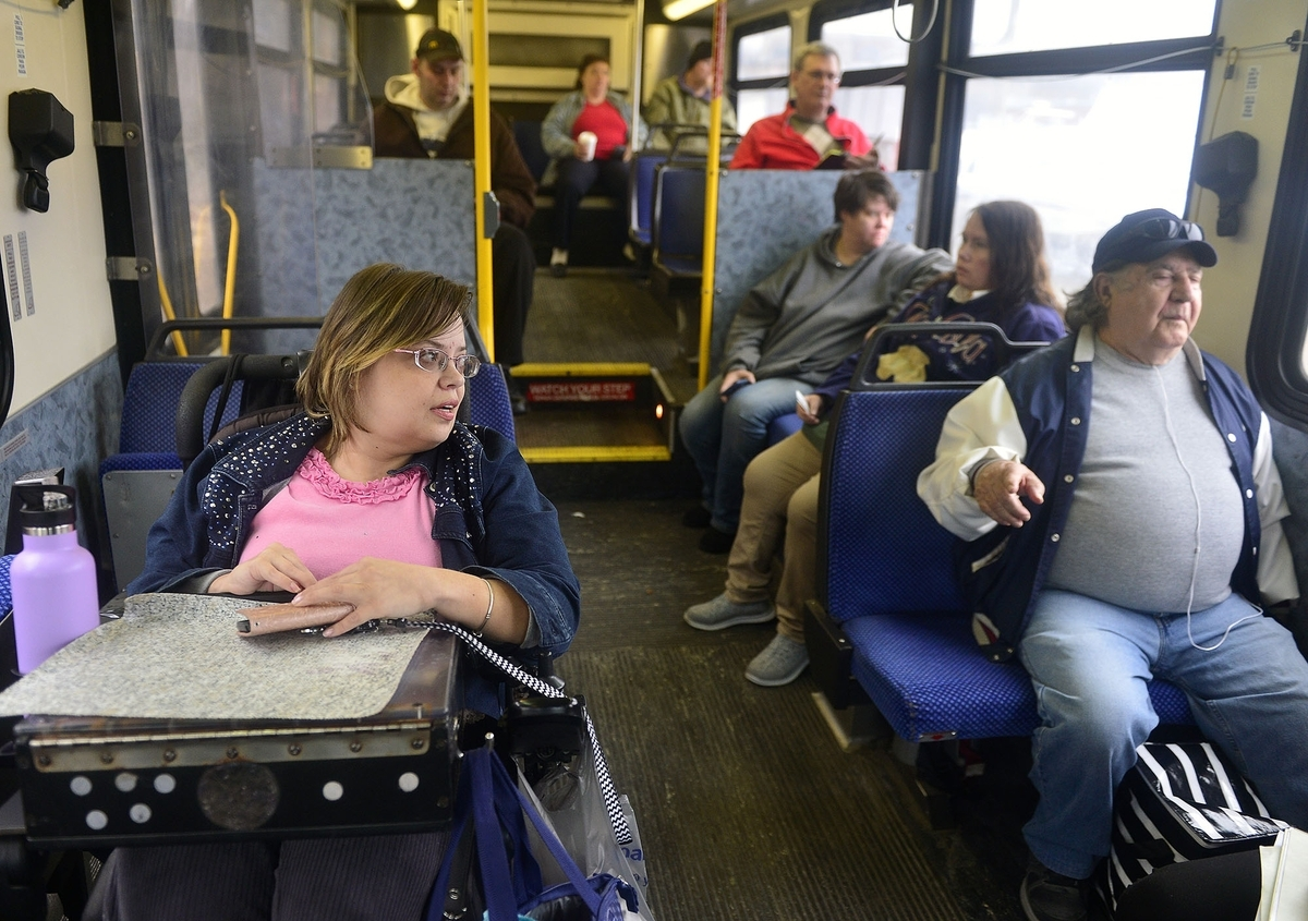 <b></b> Jennifer Lortie, left, a Canterbury resident who has cerebral palsy, talks with fellow passenger Mike Gleason of Taftville as they ride the Route 9 Southeast Area Transit District bus on Thursday, Feb. 15, 2018.