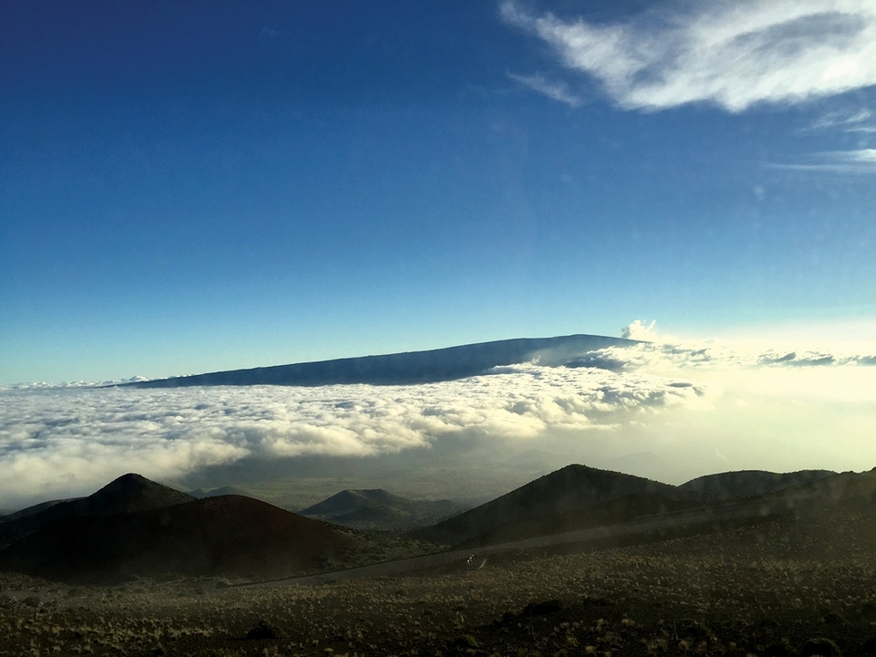 Mauna Loa is seen as rising out of the clouds from the summit of nearby Mauna Kea.