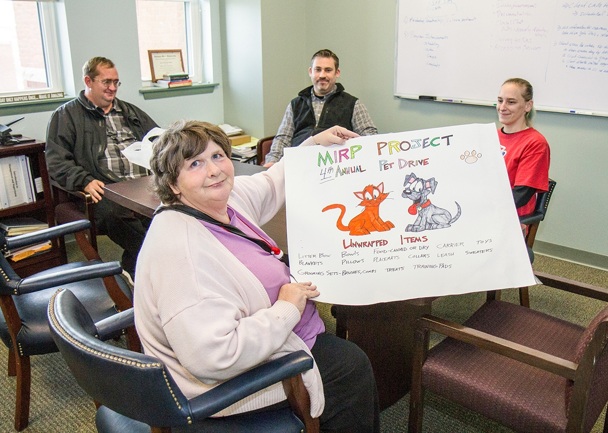 Angela, a Sound Community Services client, displays the poster she drew for the annual pet supply drive she founded, to benefit local animal shelters during a recent interview at Sound Community Services' New London headquarters. (Renee Trafford photo)