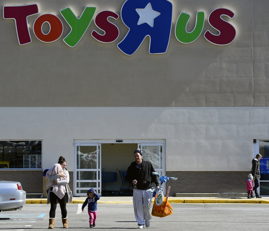 <b></b> From left, Michelle Mahoney carries her daughter Tenli, 6 months, as she walk through the parking lot with daughter Luci, 2, and husband, Patrick, all of East Lyme, on Thursday, March 15, 2018, at the Toys R Us in Waterford. The company has announced it is closing all of its Toys R Us and Babies R Us stores in the United States.