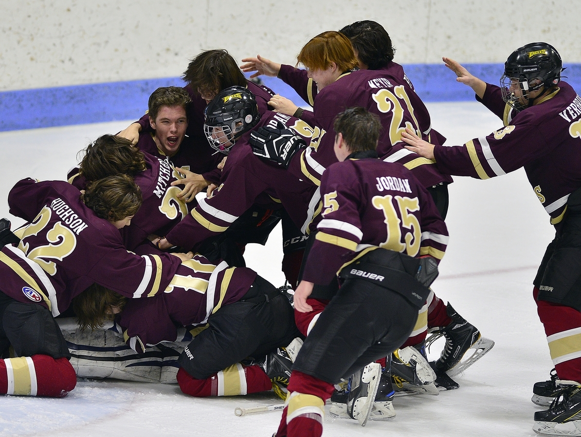 <b></b> Eastern Connecticut Eagles teammates pile on goalie Rylin Fowler after defeating Tri-Town 7-3 in the CIAC Division III hockey final on Saturday at Yale University's Ingalls Rink. It was the first title in program history for the Eagles, a cooperative program of eight local schools. (Sarah Gordon/The Day)