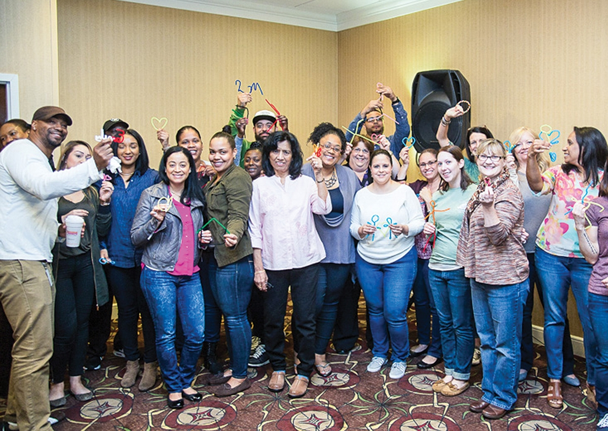 Sound Community Services staff smile during an exercise at an all-staff meeting. They were asked to put their feelings about their work into pipe cleaner figures; among the creations were peace signs, hearts, and people holding hands. (Submitted photo)