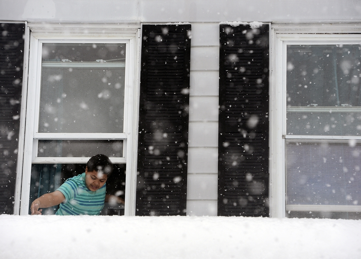 <b></b> The fourth winter snowstorm this month is expected to dump at least 5 inches and as many as 14 inches on southeastern Connecticut on Wednesday afternoon and evening. Paulie Perez Hughes is pictured measuring snow accumulation on the roof during the March 13 snowstorm. (Sarah Gordon/The Day)