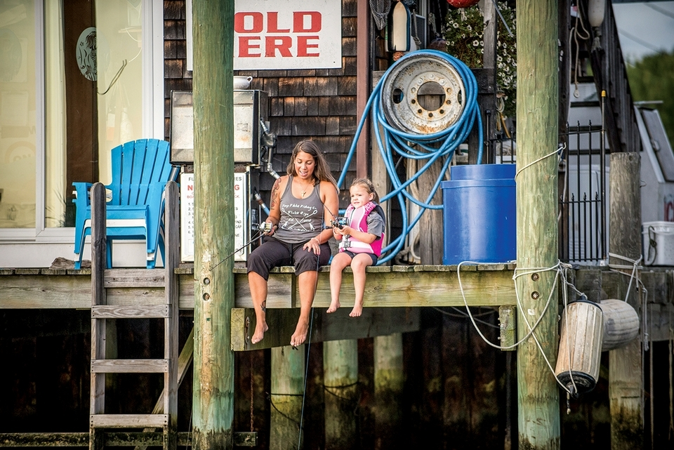 Stephanie and Sydney fish off the dock at Three Belles Marina in Niantic. Three Belles Outfitters carries her line. (Seth Jacobson photo)