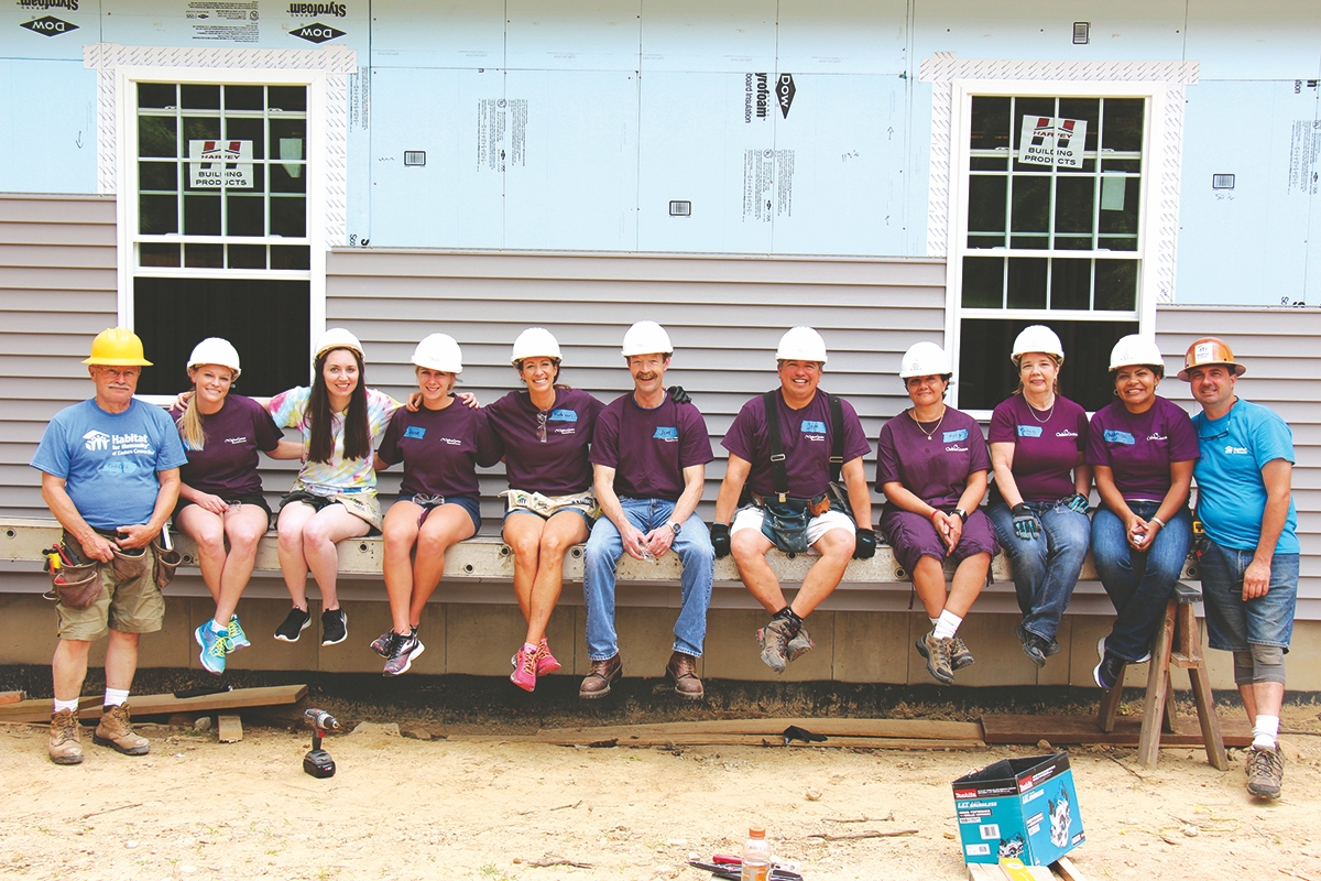 The Chelsea Groton team works diligently for members of the community inside and outside the office. Here they are with Habitat for Humanity build leaders, volunteering their time to help build a home this summer. (Submitted photo)