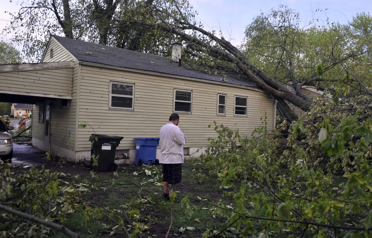 <b></b> Dominick Damiano III examines the damage to his home, 58 Great Plain Road in Norwich, after several trees fell onto the roof during a storm Tuesday, May 15, 2018. Damiano purchased the house 15 days ago.  (Tim Martin/The Day)