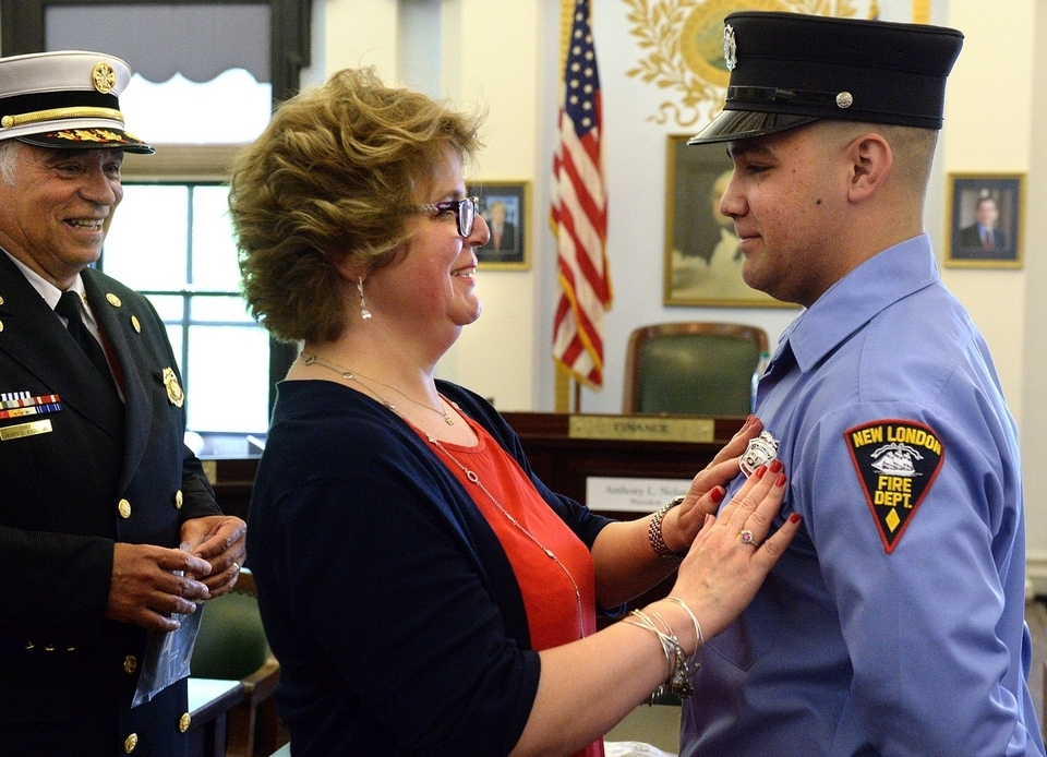 Brian DeSilva has his badge pinned on by his mother, Christine Baga of Taftville while Chief Henry Kydd looks on during the New London Fire Department swearing-in ceremony at City Hall on Wednesday, May 16, 2018.  Nicholas Petrizzi III and Markeno Grant also were sworn in Wednesday. The hiring of the three new fire department members was made possible by a Federal Emergency Management Agency Staffing for Adequate Fire and Emergency Response grant.  (Dana Jensen/The Day)