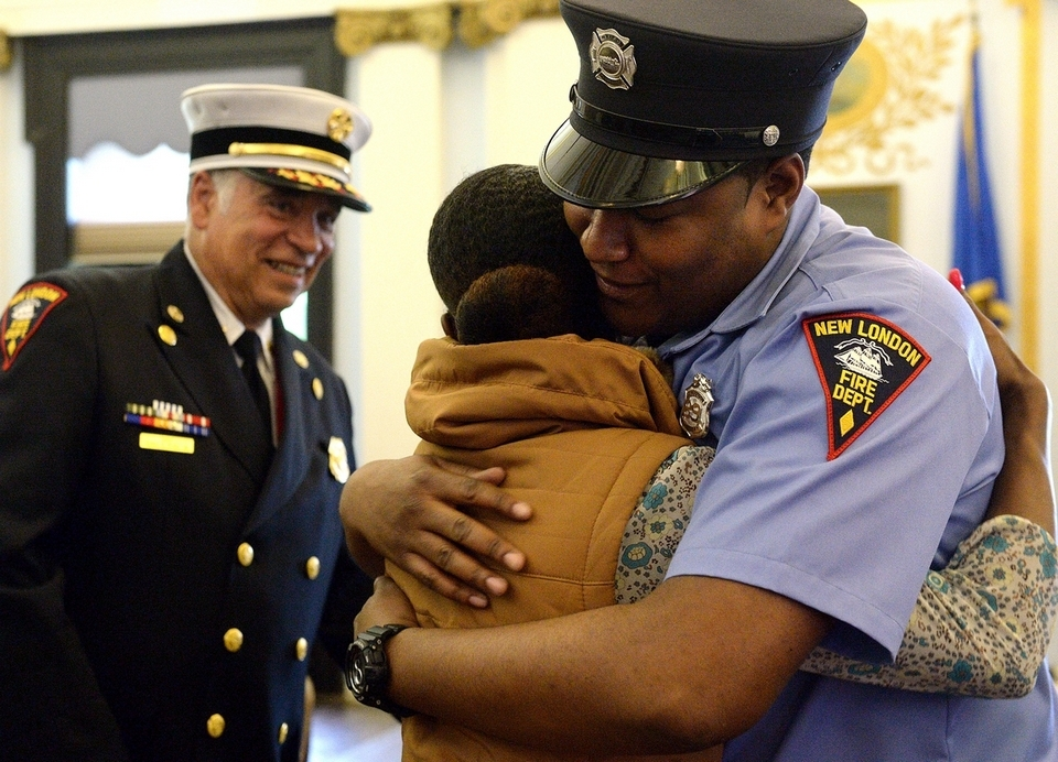 Markeno Grant and his girlfriend, Tayana Rodgers of New London, hug while Chief Henry Kydd looks on, after she pinned on Grant's badge during the New London Fire Department swearing-in ceremony at City Hall on Wednesday, May 16, 2018. Nicholas Petrizzi III and Brian DeSilva also were sworn in Wednesday. The hiring of the three new fire department members was made possible by a Federal Emergency Management Agency Staffing for Adequate Fire and Emergency Response grant.  (Dana Jensen/The Day)