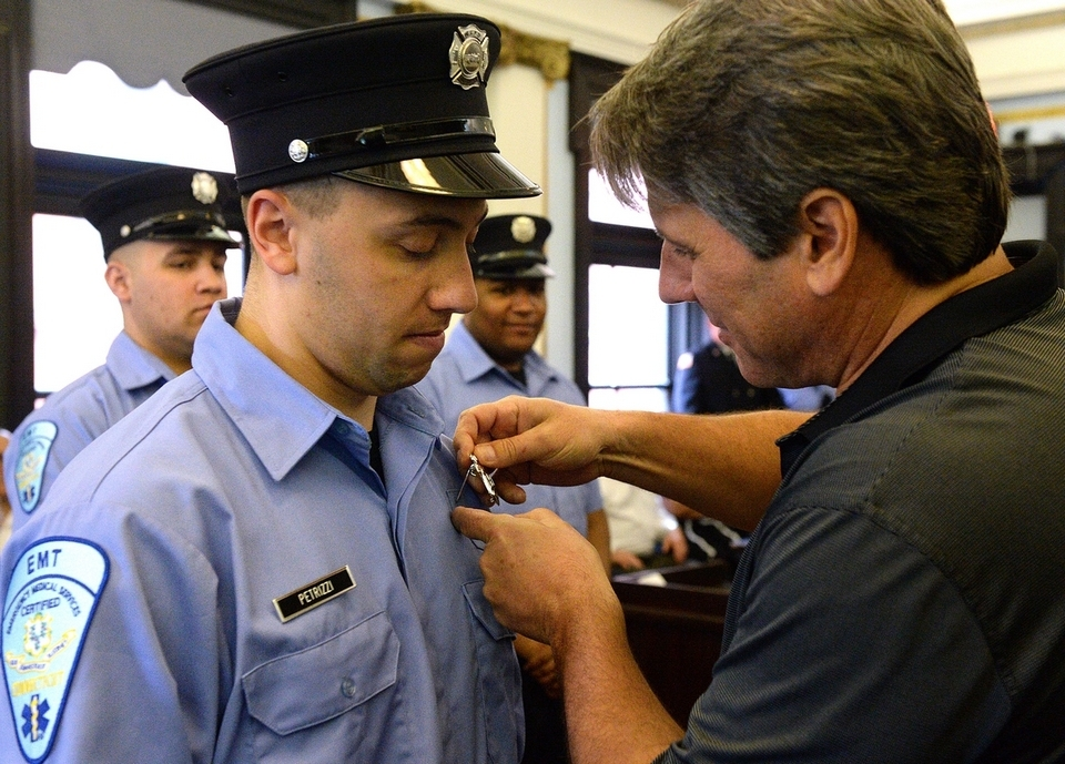 Nicholas Petrizzi III, left, has his badge pinned on by his father, Nicholas Petrizzi Jr., during the New London Fire Department swearing-in ceremony at City Hall on Wednesday, May 16, 2018. Brian DeSilva and Markeno Grant also were sworn in Wednesday. The hiring of the three new fire department members was made possible by a Federal Emergency Management Agency Staffing for Adequate Fire and Emergency Response grant.  (Dana Jensen/The Day)