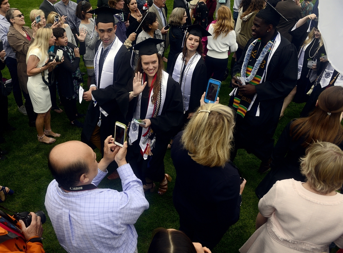 <b></b> Graduates wave as they walk through a crowd of family and friends during the processional of Connecticut College's Commencement on Sunday, May 20, 2018, at the school's Tempel Green.  (Sarah Gordon/The Day)