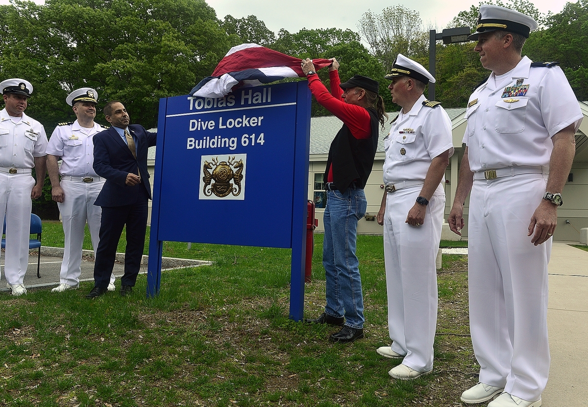 <b></b> Commissioner Thomas Saadi, left, with the Department of Veterans Affairs, and Gary Tobias lift the flag from a sign as Tobias Hall is dedicated during a ceremony on Tuesday, May 22, 2018, at the Naval Submarine Base in Groton.  The dive locker was named for Gary's sister, Donna Tobias, who was the Navy's first female hard hat diver.  (Sarah Gordon/The Day)
