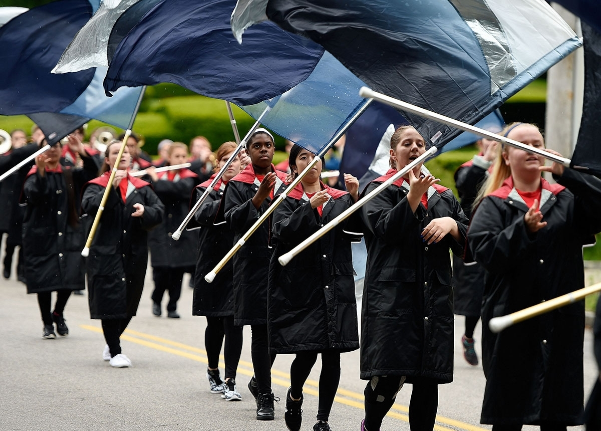 <b></b> The Norwich Free Academy marching band color guard toss their flags as they march in the Norwich Area Veterans Council Memorial Day Parade last year. (Sean D. Elliot/The Day)