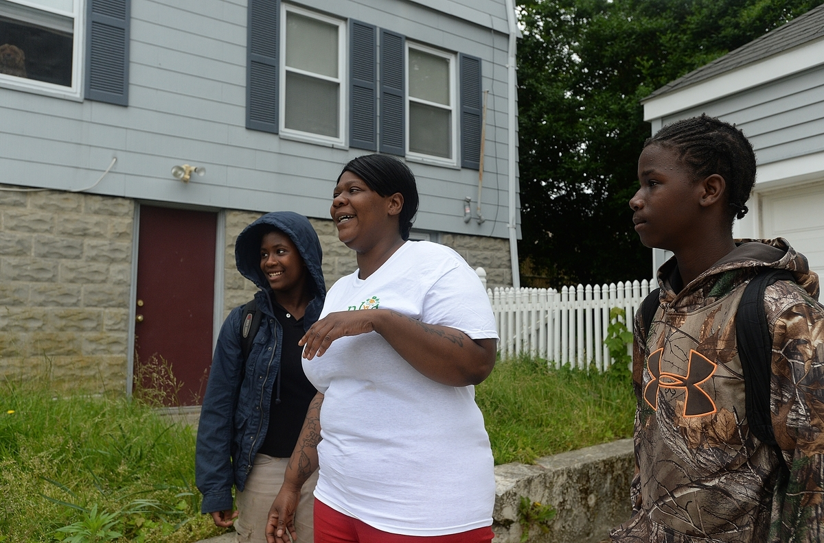<b></b> Jeanne Ward, center, and her twins, Jeanique, left, and Jahliek Turner, right, 12, stand in the driveway of their New London home on Wednesday, June 13, 2018, and talk about living in a house after they and dozens of former Thames River Apartments residents were relocated.  (Dana Jensen/The Day)