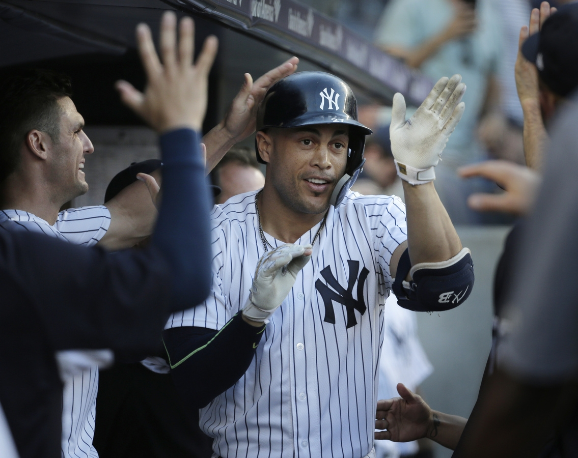 <b></b> Giancarlo Stanton is greeted by teammates after hitting a solo home run during the first inning, the first of four hit by the Yankees during Tuesday night's 7-2 win over the Seattle Mariners at Yankee Stadium in the Bronx. (AP Photo/Seth Wenig)