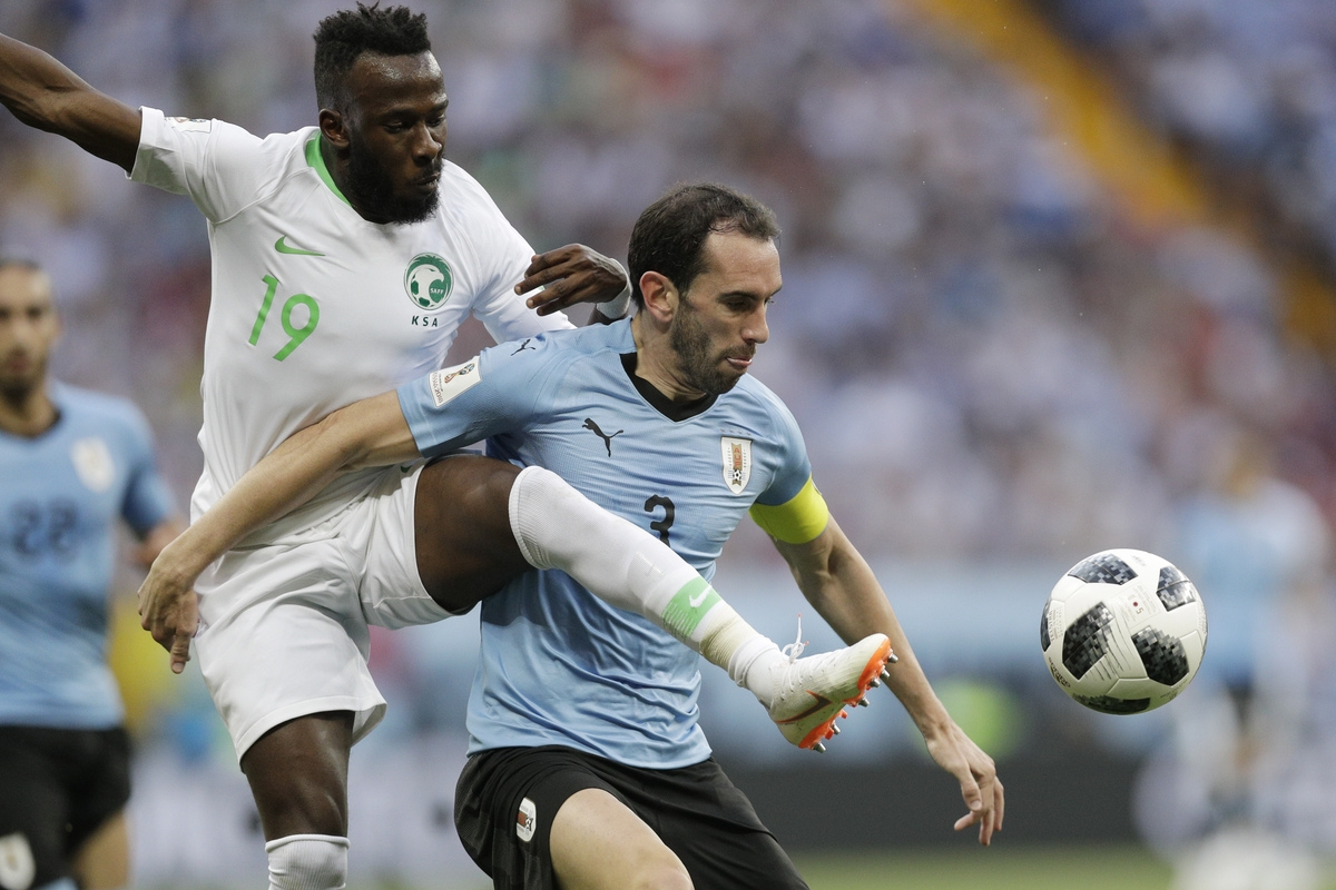 <b></b> Saudi Arabia's Fahad Almuwallad charges on Uruguay's Diego Godin during the group A match between Uruguay and Saudi Arabia at the 2018 soccer World Cup in Rostov Arena in Rostov-on-Don, Russia, on Wednesday, June 20, 2018. (Andrew Medichini/AP Photo)
